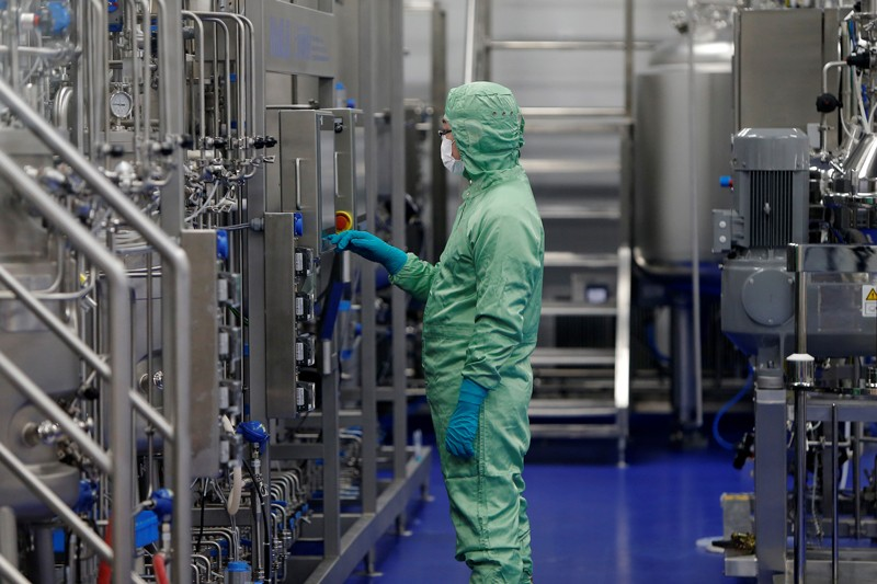 A technician in protective clothing looks at machinery at a vaccine manufacturing facility in China