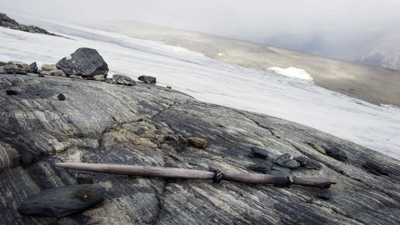 A wooden stick on a rock outcrop next to an expanse of ice.