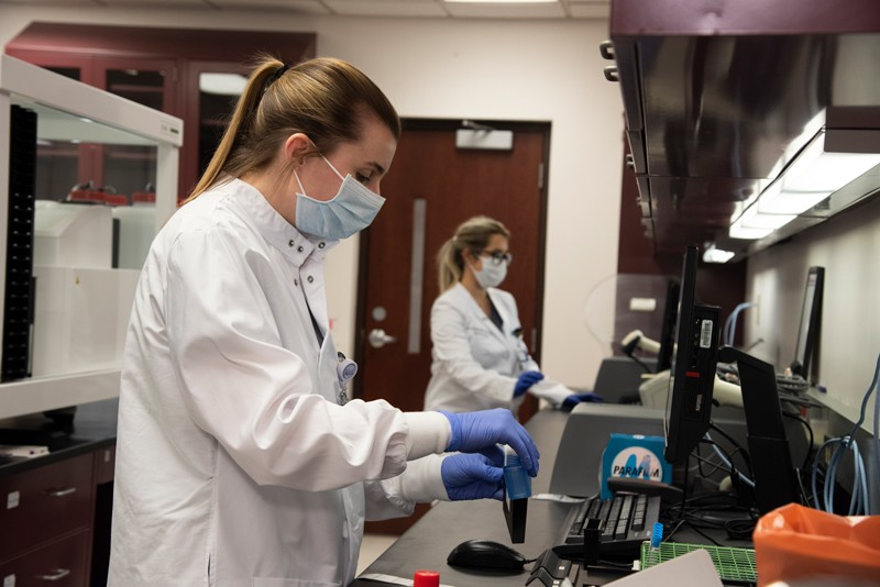 A medical technologist wearing a face mask runs validation testing on new antibodies testing equipment