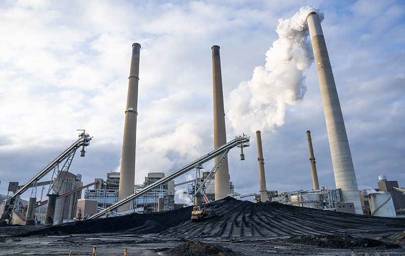 Coal is piled as emissions rise from a smoke stack at the Conesville Power Plant in Ohio, USA