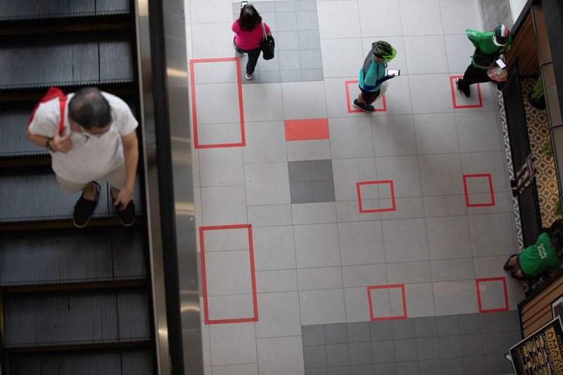 A man on an escalator looks down at people standing in squares marked on the floor as part of social distancing measures.