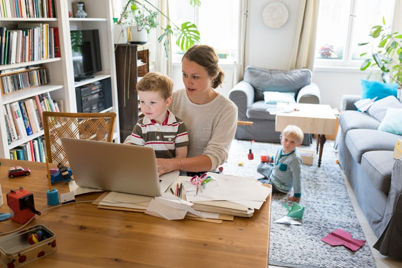 Female professional with two sons working at home.