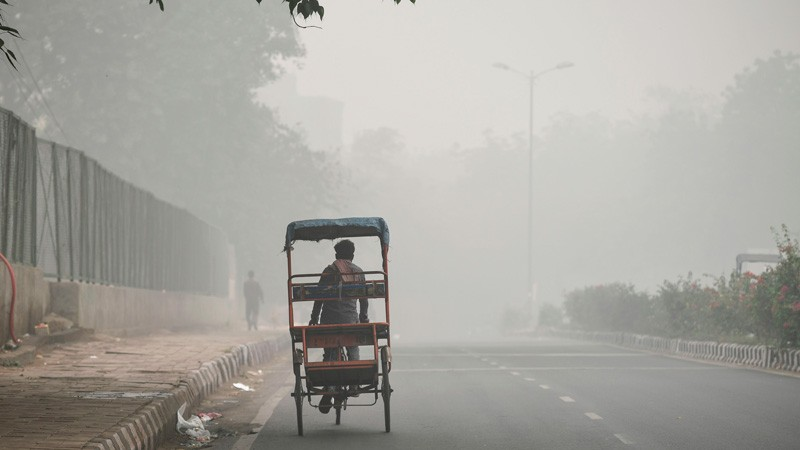 A rickshaw puller rides along a road under heavy smog conditions in New Delhi.