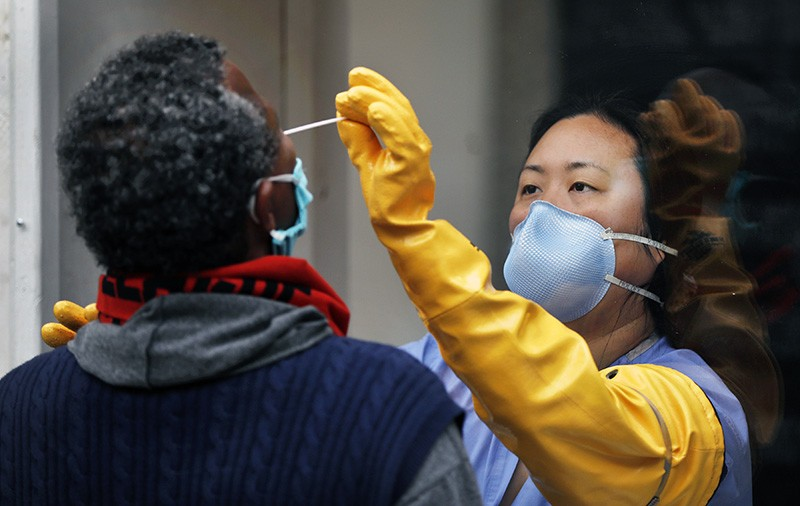 A nurse practitioner takes swab samples from a person in Los Angeles, California