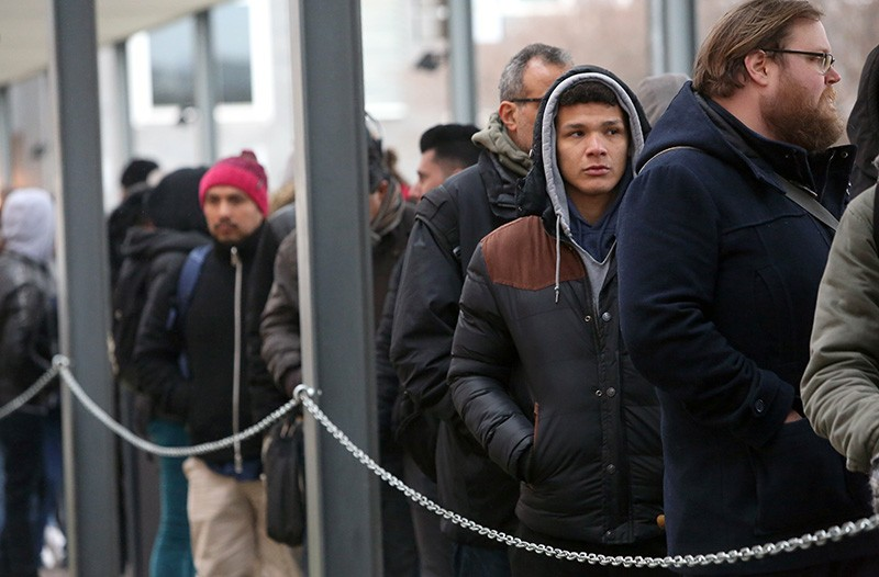 Foreigners wait in line outside the Berlin Immigration Office in Germany