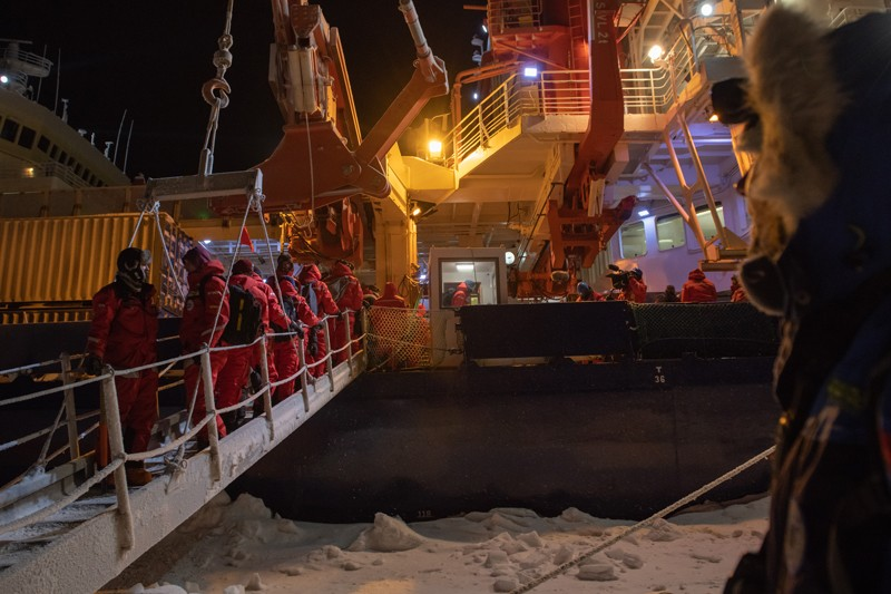 In darkness a group of people dressed in red cold weather clothing move up a gangway onto the Polarstern research vessel