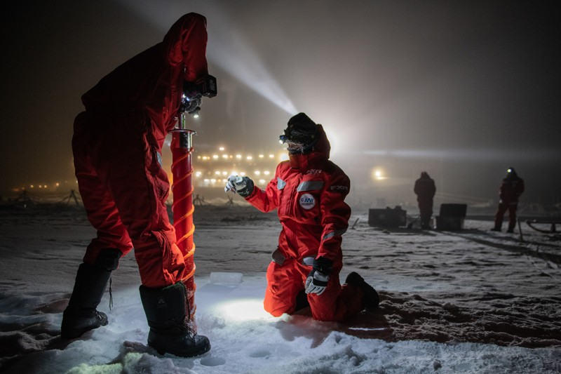 In darkness scientists collect samples from the ice sheet with the Polarstern research vessel in the distance