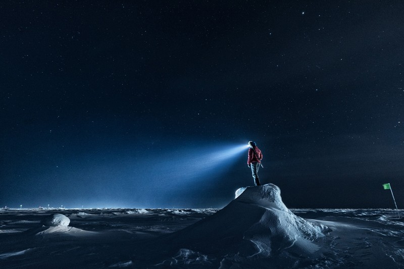 A guard stands on a mound of snow overlooking the surrounding ice sheet as the beam of a head torch shines against a black sky