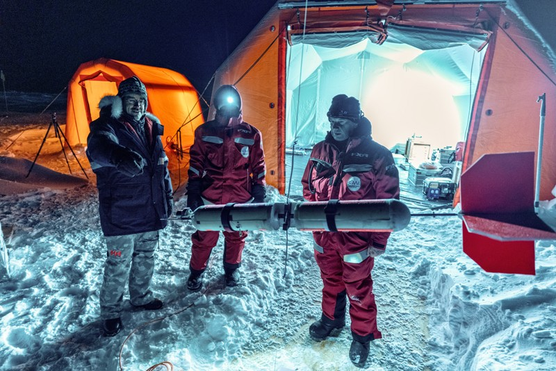 Three scientists in stand in front of tents on the ice looking an aerial instrument equipped with atmospheric sensors