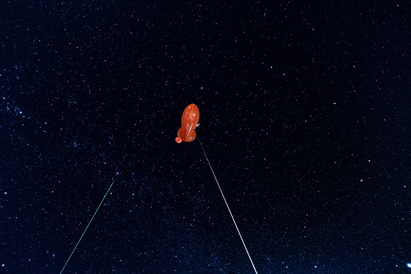 A tethered orange zeppelin used for making atmospheric measurements pictured against a starry sky with a green laser beam