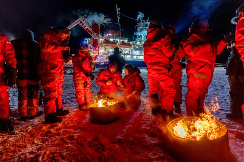 Members of the MOSAiC expedition Leg 2 team stand around bonfires on the ice with the Polarstern ship in the background