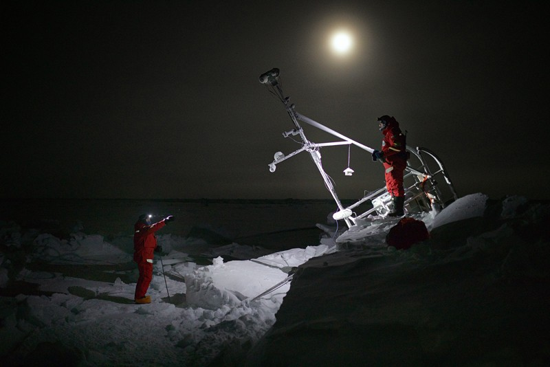 Members of the MOSAiC expedition Leg 2 team stand on an overturned sled buried in snow during the Arctic polar night