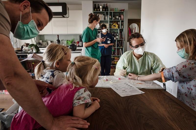 O profissional de saúde tira amostras de sangue de uma família usando máscaras sentadas à mesa de jantar em sua casa em Munique