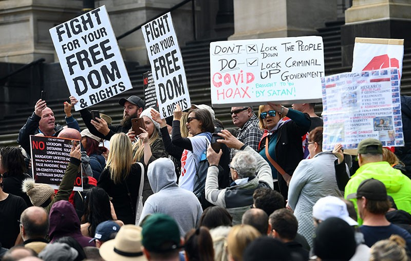 Anti-lockdown protesters hold placards on the steps of Victoria's state parliament in Melbourne