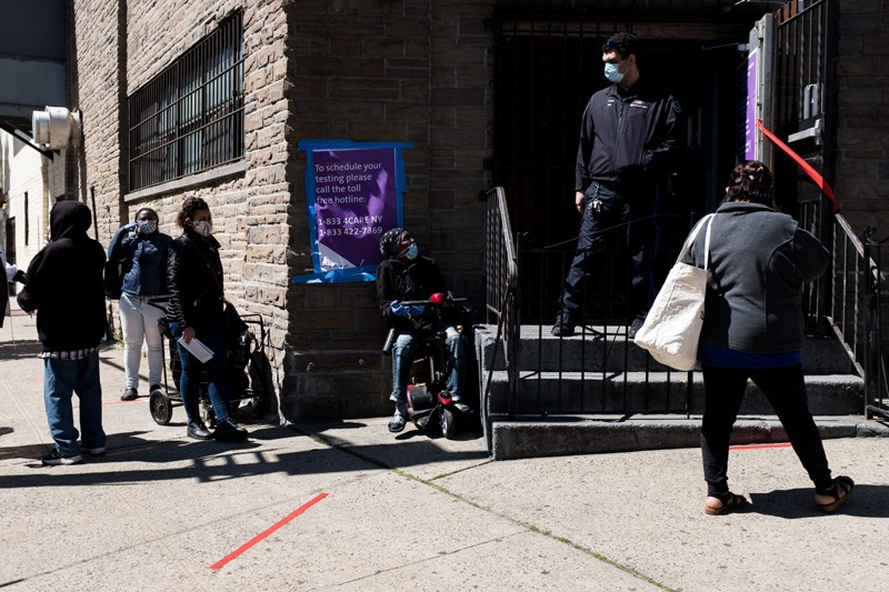 People wait in line outside of a church before getting tested for coronavirus