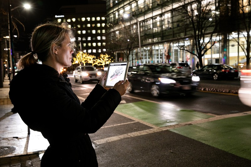 Jessika Trancik uses the CarbonCounter app on a tablet on the street in Cambridge