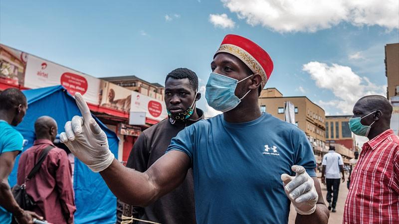 Volunteers make sure people wash their hands before entering Nakasero market in Kampala, on April 1 2020.