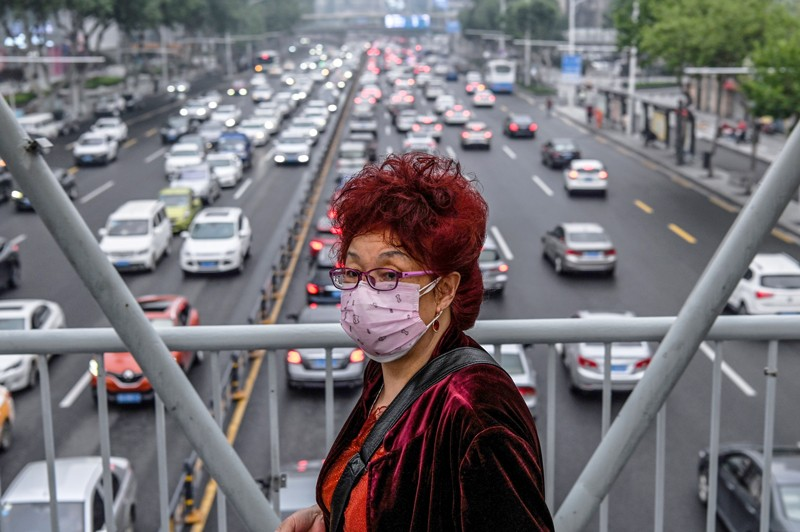 A woman wearing a facemask walks on a pedestrian bridge while traffic congestion is seen on a road in Wuhan