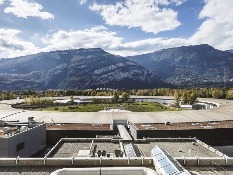 Building roof in front of synchrotron's ring-shaped roof, vegetation in centre of ring and mountains in background.