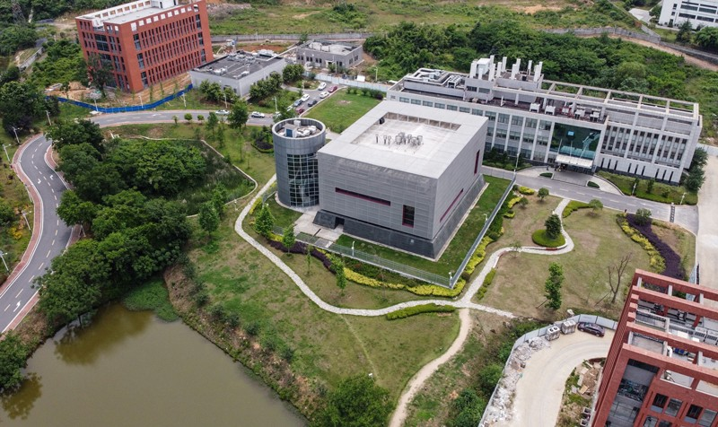 Aerial shot of a complex of modern academic buildings surrounded by trees and grass.