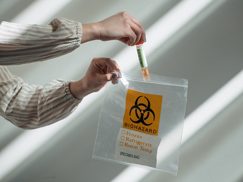 A research scientist puts a home sample test for novel coronavirus in a biohazard bag.