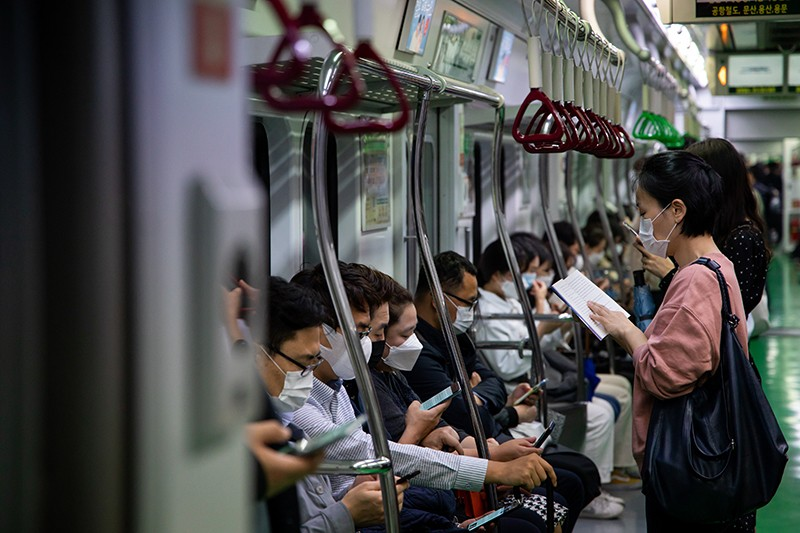 Passengers wearing protective masks ride a subway train in Seoul, South Korea