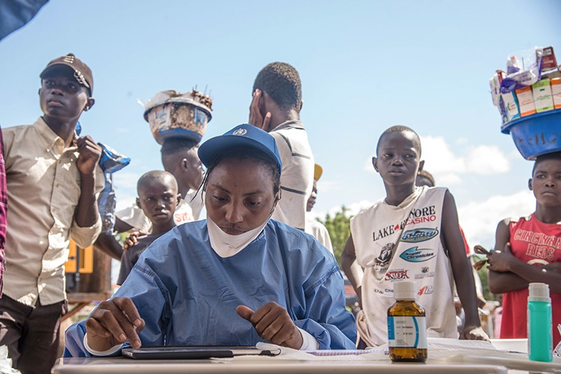 A health worker records information on a tablet as people queue to be seen.