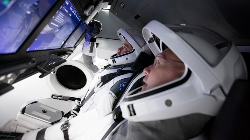Astronauts Bob Behnken and Doug Hurley wearing space suits and helmets touch control panels during a flight simulation