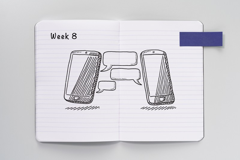 Open notebook with a sketch of two smartphones and speech bubbles