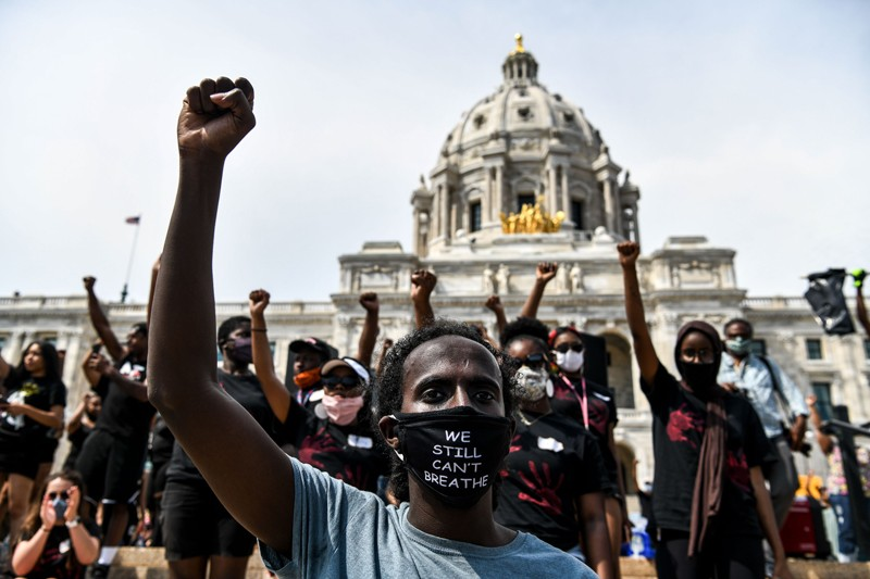 Demonstrators raise their fists outside the State Capitol of Minnesota during a protest over the death of George Floyd