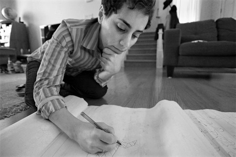 Maryam Mirzakhani writing on paper while on the floor