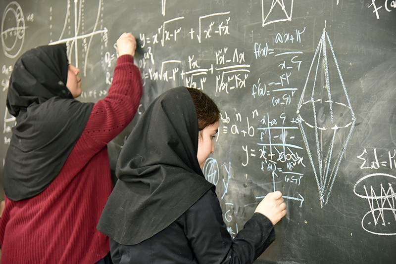 Schoolgirls in Tehran at a blackboard working on maths