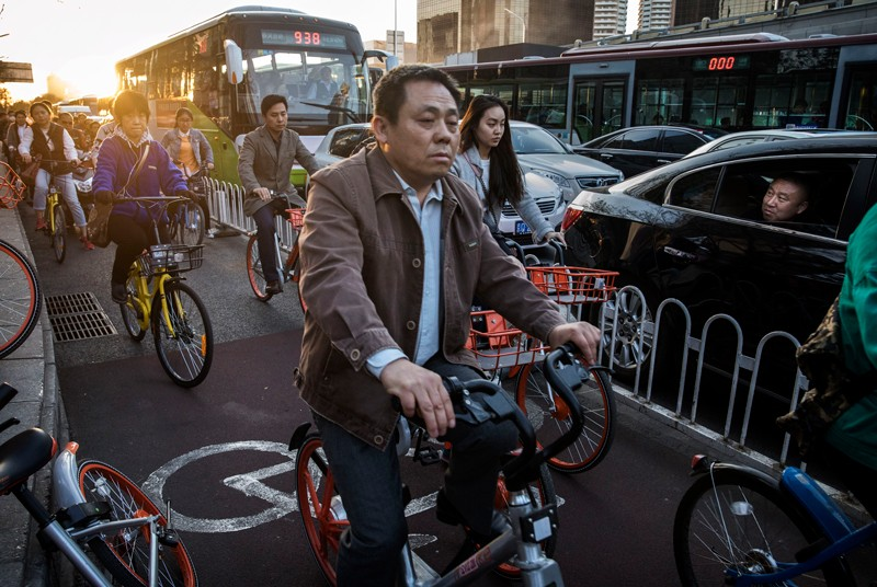 A man watches from a car as Chinese commuters crowd the bicycle lane as they ride bike shares during rush hour