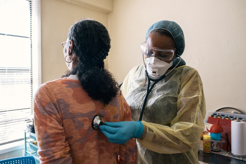 A respiratory therapist in protective clothing uses a stethoscope to listen to the lungs of a patient with asthma