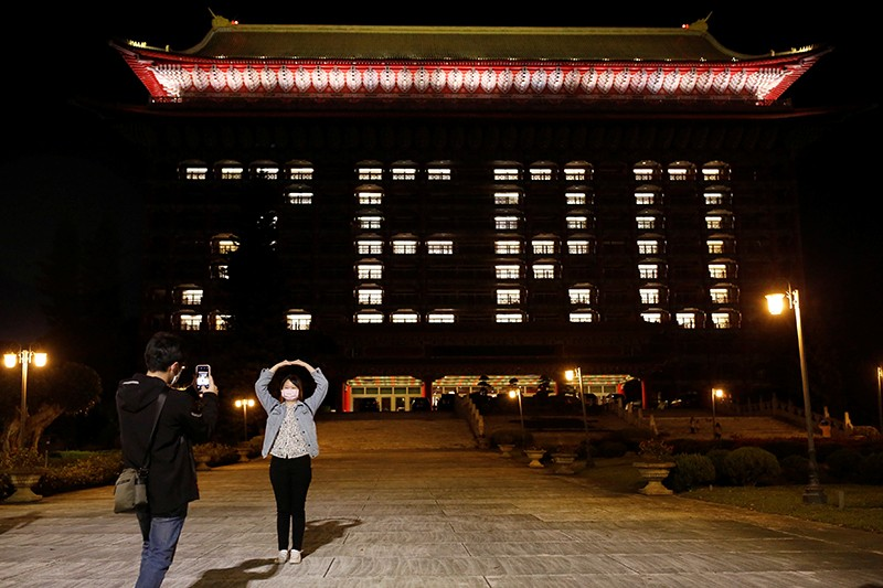 The Grand Hotel uses hotel room lights to celebrate zero confirmed cases in Taipei, Taiwan, as visitors outside take photos.
