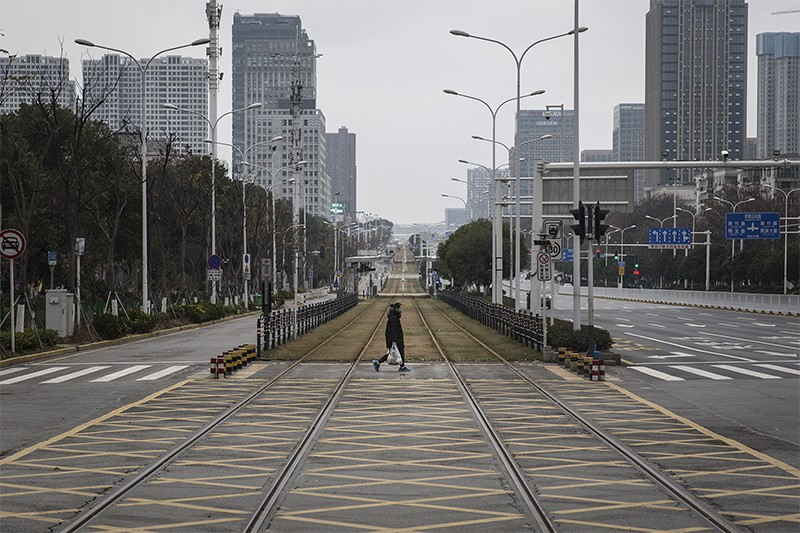 Photo of a person walking across an empty track in Wuhan, China.