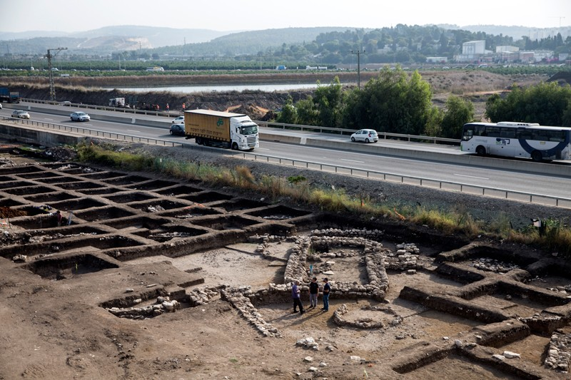 Cars and lorries travelling on a main road passing close by an archeological excavation site