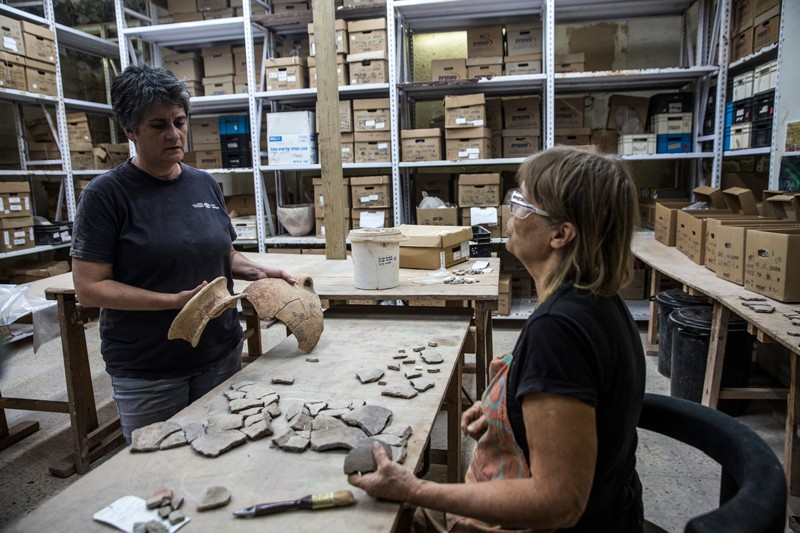 Two archaeologists examine pieces of pottery in a warehouse with boxes stacked on high shelves