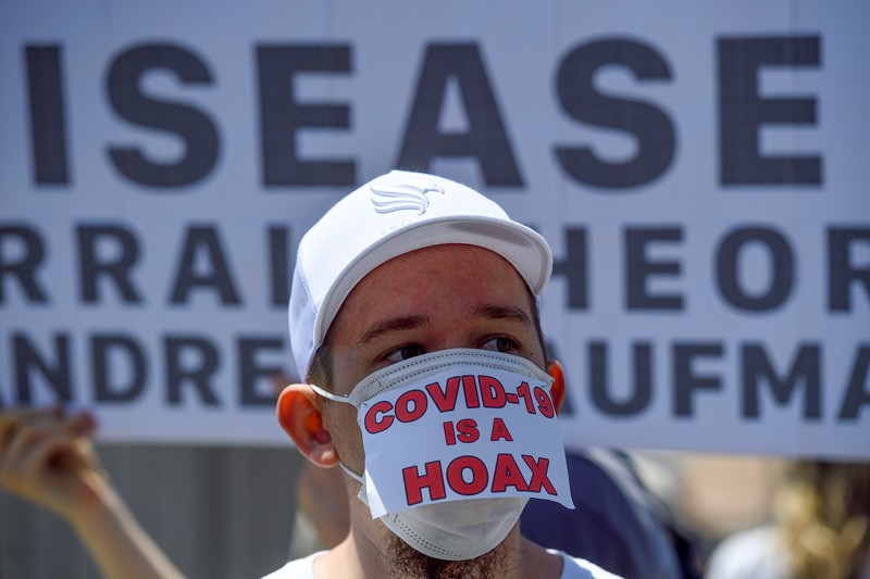 A man wears a 'COVID-19 is a hoax' mask