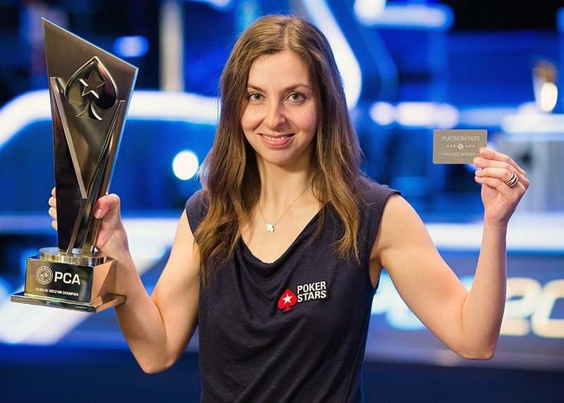 A woman holding up her trophy and playing pass from a poker championship