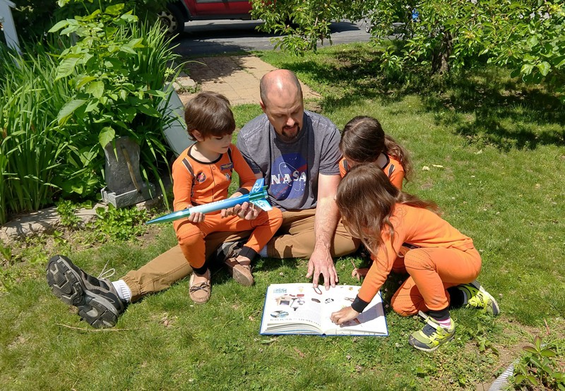 Jeremy Grabbe reads from a book while sitting on the lawn with his triplets who are wearing matching spacesuit outfits