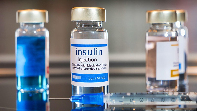 Bottle of Insulin injection with a syringe on black table and stainless steel background.