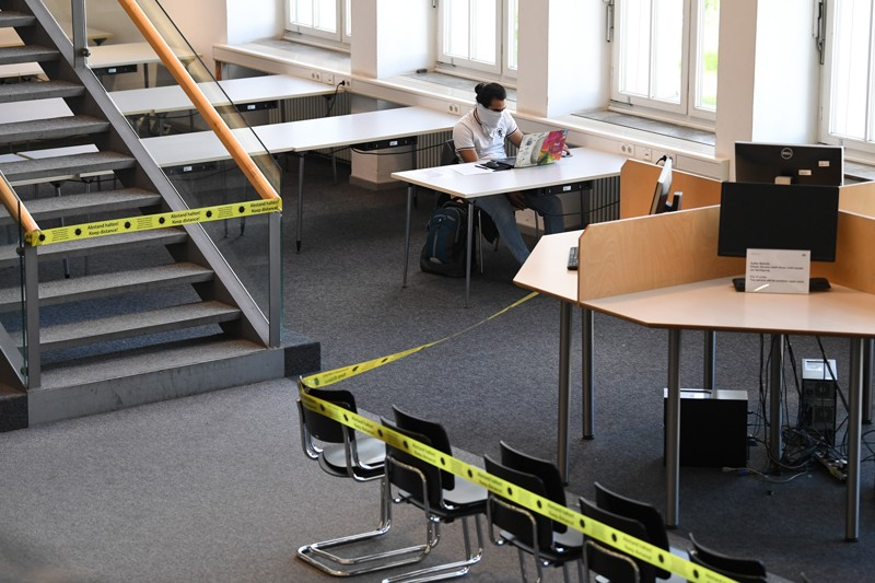 A student works on a laptop surrounded by empty desks with areas cordoned off with yellow tape.