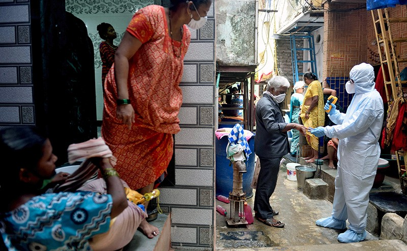 A health-care worker protective gear checks a passer-by's temperature. Women in saris and other Indian dress look on.