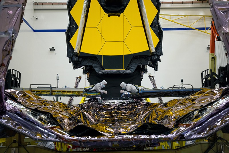 Two technicians inspect a critical part of the James Webb Space Telescope