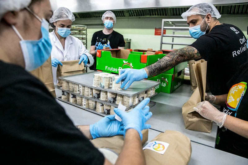People in hair nets, face masks and gloves pack cartons into paper bags.