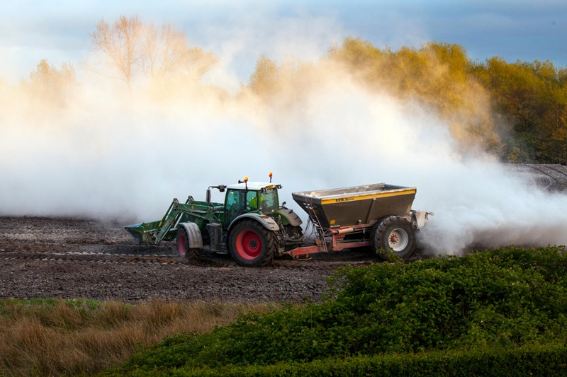 Farmer lime spreading with a tractor