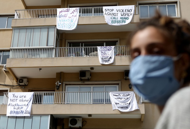 A masked Lebanese woman walks past a building with banners hanging from balconies, carrying messages against domestic violence
