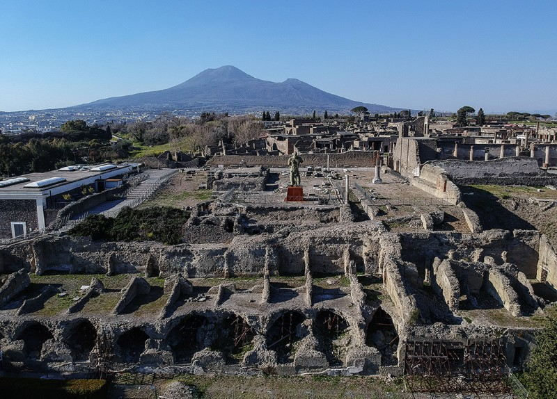Excavations of ancient ruins in Pompeii, Campania region, Italy, with the volcano Vesuvius in the background.