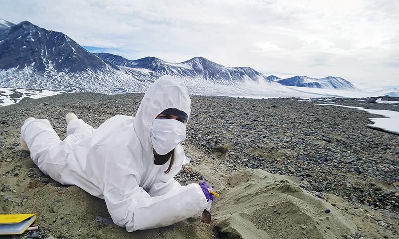A researcher in protective gear searches for traces of ancient microbial life in the Antarctic Dry Valleys.